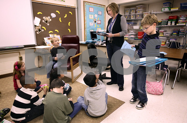 Kyle Bursaw – kbursaw@daily-chronicle.com<br /> <br /> Zach Korper helps North Elementary teacher Amy Gehant hand out blank books and awards on the last day of after school writing club. The club is for first grade students and Korper, a third-grader, helped with the club because of his strong interest in writing. One of the books Korper wrote is being made into an episode of Green Screen Adventures.