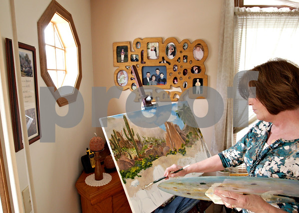 Beck Diefenbach  -  bdiefenbach@daily-chronicle.com<br /> <br /> Painter Patty Raih works on her impressionist vista of a Southwest desert in the living room of her home in DeKalb, Ill., on Monday May 17, 2010. Raih will have her work on display at this weekend's Kishwaukee Valley Art League's Northern Illinois Art Show on the lawn of the DeKalb County Courthouse in Sycamore, Ill.