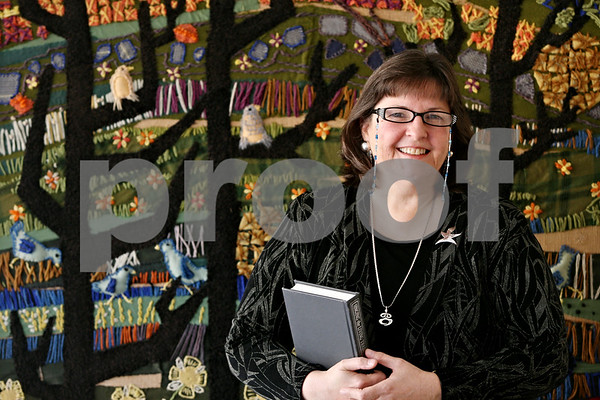 Rob Winner – rwinner@daily-chronicle.com<br /> <br /> The Rev. Linda Slabon of the Unitarian Universalist Fellowship of DeKalb stands before a quilt that was created by some of the first members of the congregation about 50 years ago.<br /> <br /> Wednesday September 29, 2010<br /> DeKalb, Ill.