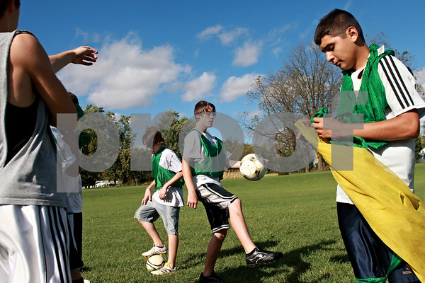 Beck Diefenbach – bdiefenbach@daily-chronicle.com<br /> <br /> Hiawatha freshmen Gage Grant (center left) and Taylor Edwards (center right) juggle soccer balls before practice at Benke Park in Kirkland, Ill., on Friday Sept. 24, 2010. This is Hiawatha's first soccer team.