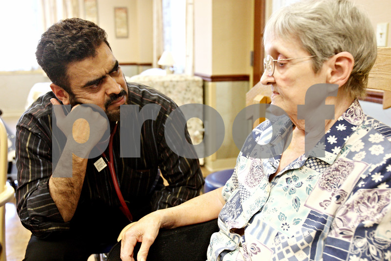 Rob Winner – rwinner@daily-chronicle.com<br /> <br /> Dr. Shakeel Ahmad, of the DeKalb Clinic, speaks with Barbara Owen, of DeKalb, about her condition at the Pine Acres Rehab and Living Center in DeKalb on Tuesday. Owen injured her rotator cuff after a fall.