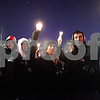 Beck Diefenbach  -  bdiefenbach@daily-chronicle.com<br /> <br /> From left, Phi sigma Kappa brothers freshman Bill Devona, junior Mark Ternstrom and junior Kyle Donoghue raise their candles during candlelight vigil at the Martin Luther King Commons on the campus of NIU in DeKalb, Ill., on Sunday Feb. 14, 2010.