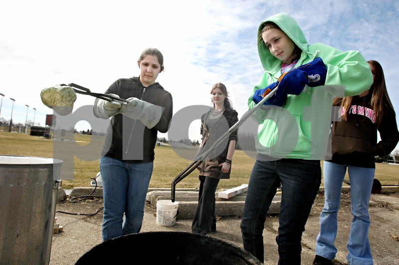 Rob Winner – rwinner@daily-chronicle.com<br /> DeKalb High School students Megan King (left), 17, and Jessica Pinon, 18, remove Raku pieces from a kiln and place them into a can filled with hay during their ceramics class on Tuesday March 16, 2010 in DeKalb, Ill.