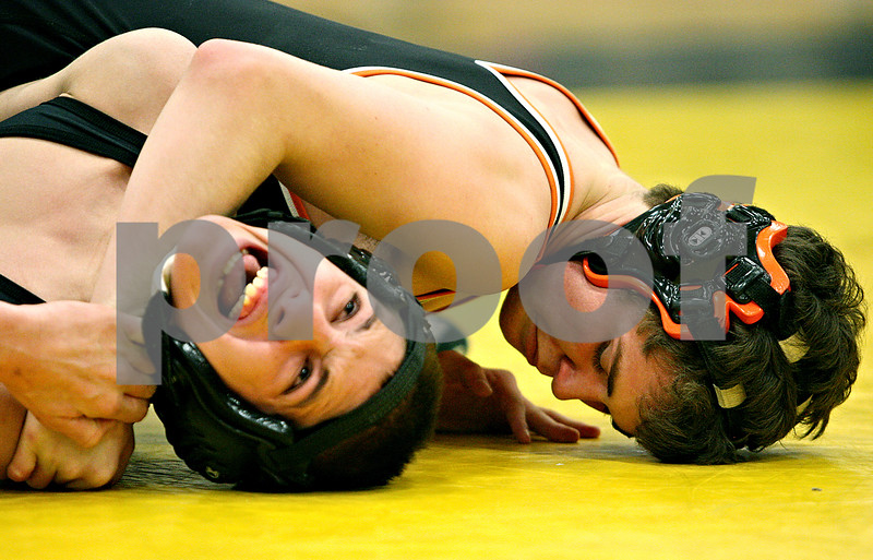 Rob Winner – rwinner@daily-chronicle.com<br /> Sycamore's Austin Zimmer (left) is held down by DeKalb's Tyler Larson during their 112-pound match in Sycamore, Ill. on Friday January 15, 2010.