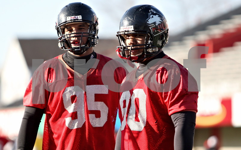 Rob Winner – rwinner@daily-chronicle.com<br /> <br /> Sean Progar (left) and Alan Baxter talk on the sidelines during NIU football practice on Tuesday March 23, 2010 in DeKalb, Ill.