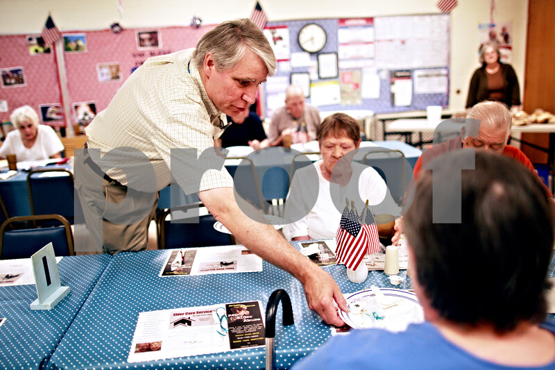 Beck Diefenbach  -  bdiefenbach@daily-chronicle.com<br /> <br /> Volunteer Dan Kenney serves attendants of the free community dinner at the VAC lunch room in the Elder Care Center in DeKalb, Ill., on Wednesday July 7, 2010.