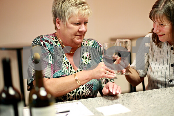 Beck Diefenbach - bdiefenbach@daily-chronicle.com<br /> <br /> Rosemary Evans (right), of DeKalb, and K.T. Barnaby, of DeKalb, clink glasses before tasting a glass of wine during Friday Night Flights wine tasting at Choice Wine and Spirits in DeKalb, Ill., on Friday Aug. 6, 2010. The tasting occurs every Friday and starts at 5 P.M.