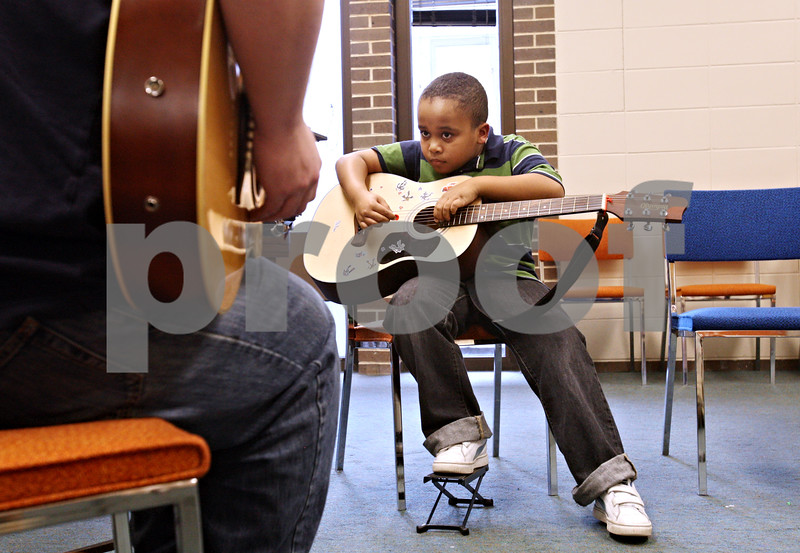 Beck Diefenbach  -  bdiefenbach@daily-chronicle.com<br /> <br /> Nicholas Chen, 8, of DeKalb, Ill., practices the guitar during a guitar basics lesson at the Northern Illinois University Community School of Music in DeKalb, Ill., on Wednesday March 17, 2010.