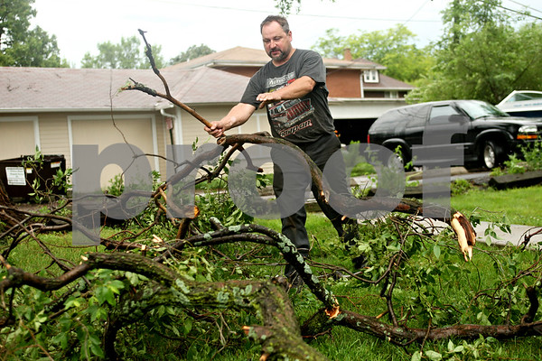 Beck Diefenbach  -  bdiefenbach@daily-chronicle.com<br /> <br /> Russ Haendel, of DeKalb, collects downed branches on his neighbor's lawn following the storm on Friday June 18, 2010