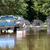 Rob Winner – rwinner@daily-chronicle.com<br /> <br /> A resident of Evergreen Village in Sycamore, Ill. exits his vehicle and makes his way through the flooded street on Saturday July 24, 2010.