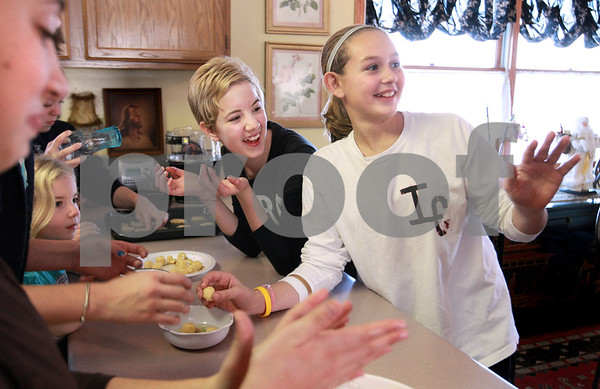 Kyle Bursaw – kbursaw@daily-chronicle.com<br /> <br /> Ivy Marcrum, center, and Madison Russell laugh at something Ivy's Mom Courtney Marcrum said while putting together cookies with several other friends to bake at the Marcrum's home in Waterman on Wednesday, Dec. 22, 2010.