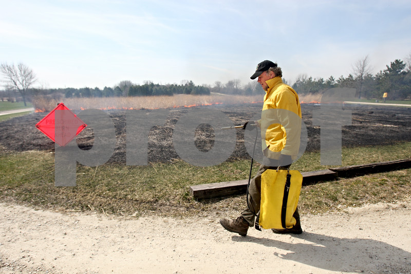 Rob Winner – rwinner@daily-chronicle.com<br /> <br /> Terry Hannan, DeKalb County Forest Preserve Superintendent, carries a polyurethane bag filled with water during a controlled burn at Afton Forest Preserve in DeKalb, Ill. on Wednesday March 31, 2010.
