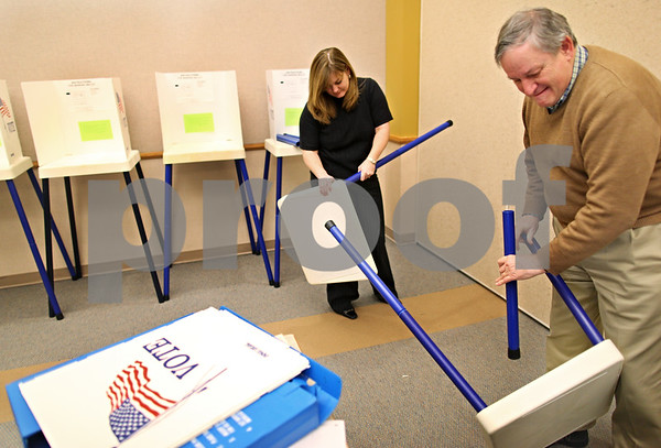 Beck Diefenbach  -  bdiefenbach@daily-chronicle.com<br /> <br /> Deputy clerk Julie Nollkamper (center) and election judge John Linderoth disassemble some of the extra voting booths near the end of the first day of early voting at the DeKalb County Legislative Building in Sycamore, Ill., on Monday Jan. 11, 2009.