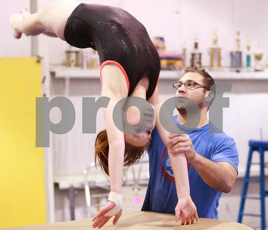 Kyle Bursaw – kbursaw@daily-chronicle.com<br /> <br /> DeKalb J.V. gymnastics coach Dustin Berman guides sophomore Breanna Burgess over the vault at Energym in Sycamore, Ill. on Tuesday, Dec. 21, 2010.