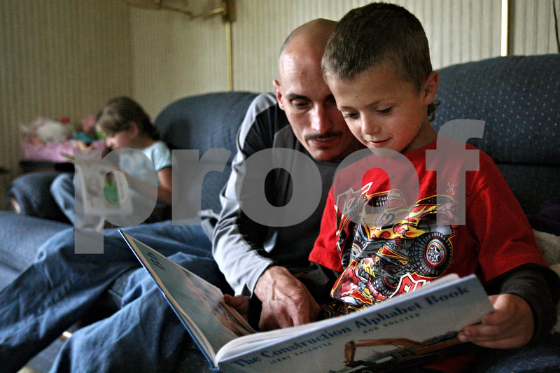 Rob Winner – rwinner@daily-chronicle.com<br /> <br /> Dameian Rozek (from right to left), 5, looks at a book with his father John as Andreana, 7, reads to herself before dinner at their home on Thursday April 7, 2010 in Sandwich, Ill.