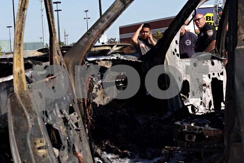 Beck Diefenbach  -  bdiefenbach@daily-chronicle.com<br /> <br /> Angel Garcia, of DeKalb, looks at his Lincoln Aviator after it was destroyed in a car fire in the Walmart parking lot in DeKalb, Ill., on Friday July 2, 2010.