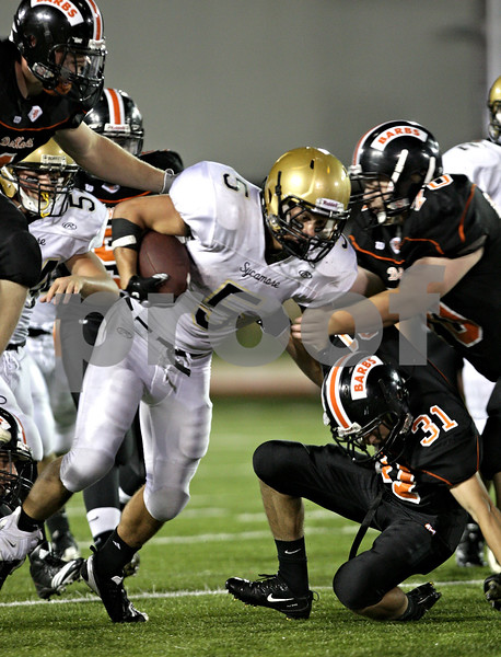 Beck Diefenbach – bdiefenbach@daily-chronicle.com<br /> <br /> Sycamore running back Eric Ray (5, center) slips through DeKalb defenders during the third quarter of the Castle Challenge football game between DeKalb and Sycamore High Schools at Huskie Stadium on the campus of Northern Illinois University in DeKalb, Ill., on Friday Sept. 10 2010.