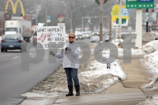 Rob Winner – rwinner@daily-chronicle.com<br /> Sue Olsen, mother of missing adult Bradley Olsen, holds a sign of her son in front of what was once Bar One on West Lincoln Highway in DeKalb, Ill. on Saturday January 16, 2010. On January 20, Bradley Olsen of Maple Park will have been missing for three years. He was last seen leaving what used to be Bar One in DeKalb.