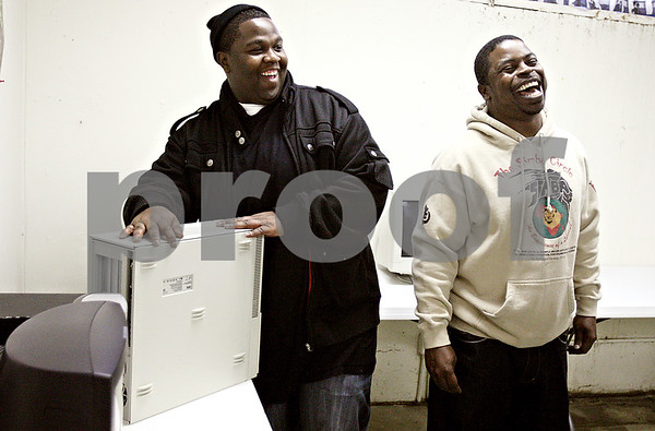 Rob Winner – rwinner@daily-chronicle.com<br /> Jarvis Pittman (left) and Anthony Chatman share a laugh while setting up a computer lab at The Rock Christian Church in DeKalb, Ill. on Monday January 18, 2010.