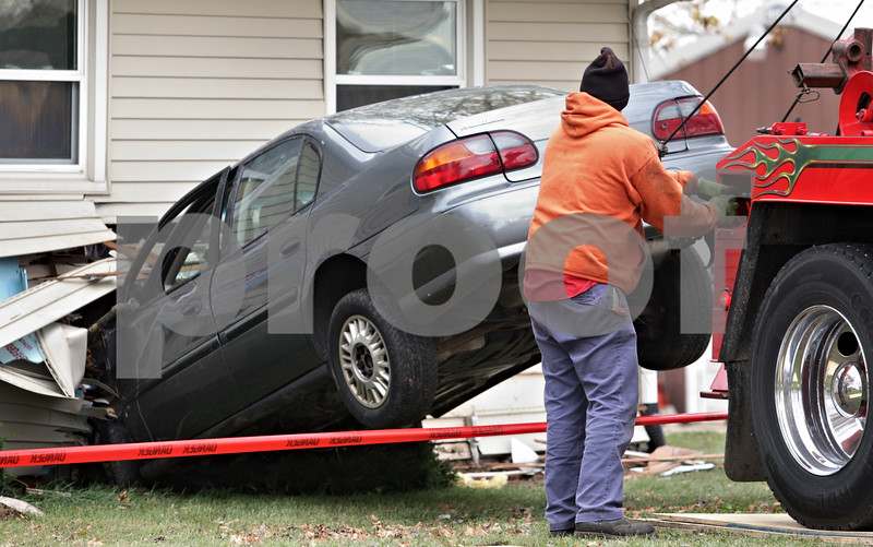 Kyle Bursaw - kbursaw@daily-chronicle.com<br /> <br /> An Allen's Towing employee uses his truck to hoist a Chevy Malibu out of the home at 2972 Route 23, just south of Genoa. 10/26/10