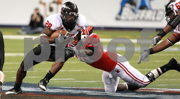 Kyle Bursaw – kbursaw@daily-chronicle.com<br /> <br /> Northern Illinois running back Chad Spann (28) tries to escape Miami (OH) linebacker Evan Harris (30) in the MAC Championship game. Miami (OH) defeated Northern Illinois 26-21<br /> at Ford Field in Detroit, Mich. on Friday, Dec. 3, 2010.