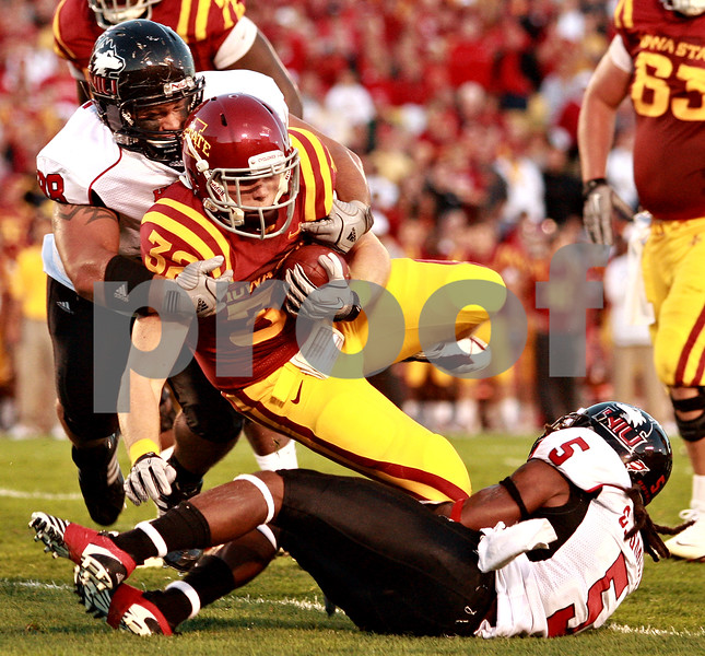Beck Diefenbach  -  bdiefenbach@daily-chronicle.com<br /> <br /> Northern Illinois defensive tackle D.J. Pirkle (98, top) and defensive back Chris Smith (5, bottom) tackle Iowa State running back Jeff Woody (32) during the first quarter of the game at Jack Trice Stadium on the campus of Iowa State University in Ames, Iowa, on Thursday Sept. 2, 2010. Iowa State defeated Northern Illinois 27 to 10.