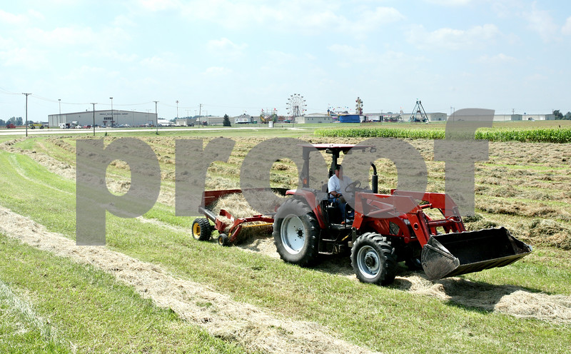 Rob Winner  -  rwinner@daily-chronicle.com<br /> <br /> On Thursday August 19, 2010, John Ward, of Sycamore, bales hay in a field near the DeKalb Taylor Municipal Airport in DeKalb, Ill. which will be used for parking by visitors to Corn Fest.
