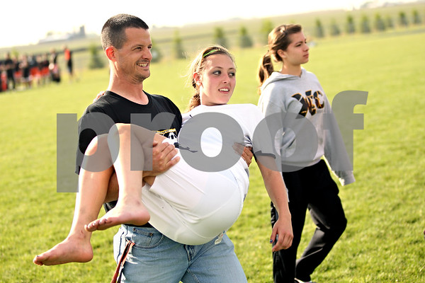 Beck Diefenbach  -  bdiefenbach@daily-chronicle.com<br /> <br /> Sycamore head coach Dave Lichamer carries an injured Sarah Papini (18) on to the field after defeating DeKalb in the IHSA Class 2A Rochelle Regional Championship at Rochelle Township High School in Rochelle, Ill., on Friday May 21, 2010. Sycamore defeated DeKalb 2 to 1.