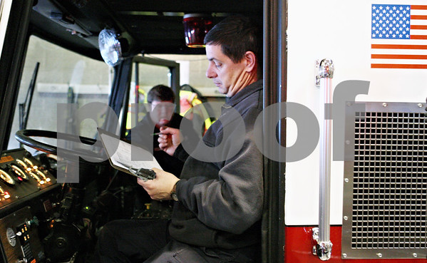 Rob Winner – rwinner@daily-chronicle.com<br /> Firefighter Drew Wells (front) and fire Capt. Kevin McCauley check over the equipment at fire station one in DeKalb, Ill. at the beginning of their shift on Friday February 26, 2010.