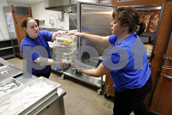 Rob Winner – rwinner@daily-chronicle.com<br /> Geness Warren (left) and Lisa Roelfsema begin preparing meals for the students of Cortland Elementary School in Cortland, Ill. on Friday February 19, 2010.