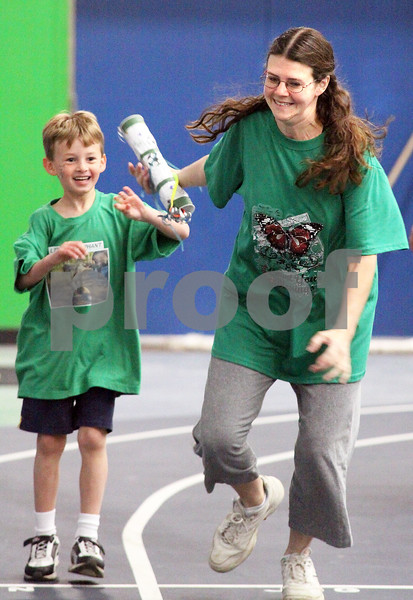 Wendy Kemp/For The Chronicle<br /> Nathan Skeens, 6, of Cortland hands the baton off to his mom, Suzanne, during the mini-relay marathon at the Kishwaukee YMCA on Saturday.<br /> Sycamore 4/18/10