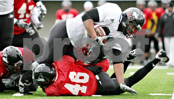 Rob Winner – rwinner@daily-chronicle.com<br /> <br /> NIU running back Cameron Bell is wrapped up while carrying the ball for a few yards during practice at Huskie Stadium in DeKalb, Ill. on Thursday April 8, 2010.