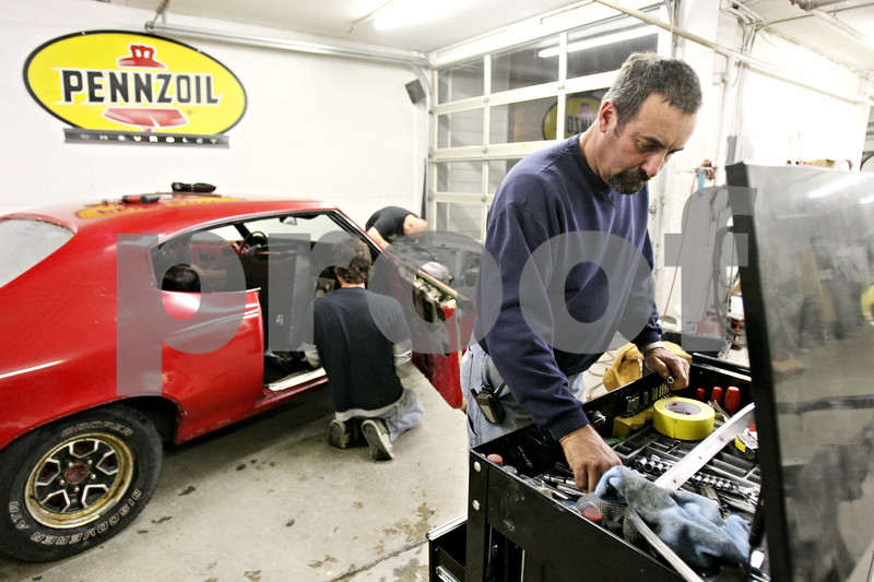 Rob Winner – rwinner@daily-chronicle.com<br /> <br /> Tim Koker searches for a tool while working on his daughter's 1970 Buick Skylark at RPM Restorations on Wednesday night. Jessica Koker is currently serving in the Navy.