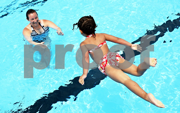 Rob Winner – rwinner@daily-chronicle.com<br /> <br /> Kate Little, of DeKalb, watches and waits for a splash as her daughter, Mikaili, 3, jumps into the pool at Hopkins Park in DeKalb, Ill. on Friday June 4, 2010. The two visit the pool every weekend.