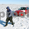 Rob Winner – rwinner@daily-chronicle.com<br /> <br /> John Sturgill of GreenCo Towing in Yorkville heads back to his tow truck after attaching a tow cable to the front of a vehicle stuck in a field off of Somonauk Road in Squaw Grove Township on Monday afternoon.