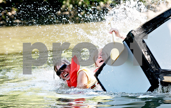 Rob Winner – rwinner@daily-chronicle.com<br /> <br /> Karinda Jennings (left) and Haley Fischer fall into the Kishwaukee River during the Kingston Fest 2010 Kardboard Boat Regatta on Saturday July 17, 2010 in Kingston, Ill.