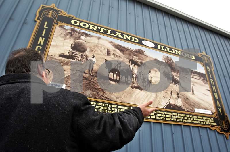 """Beck Diefenbach - bdiefenbach@daily-chronicle.com<br /> <br /> Cortland mayor Bob Seyller helps unveil a new mural on the side of Dun Rite Tool and Machine Company in Cortland, Ill., on Monday March 8, 2010. The mural recognized Cortland's role in the """"Good Roads Movement."""""""