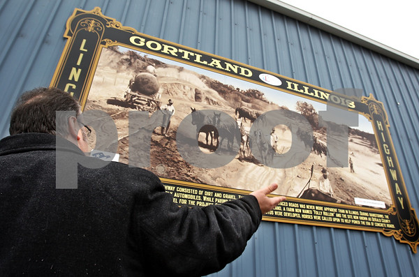"Beck Diefenbach - bdiefenbach@daily-chronicle.com<br /> <br /> Cortland mayor Bob Seyller helps unveil a new mural on the side of Dun Rite Tool and Machine Company in Cortland, Ill., on Monday March 8, 2010. The mural recognized Cortland's role in the ""Good Roads Movement."""