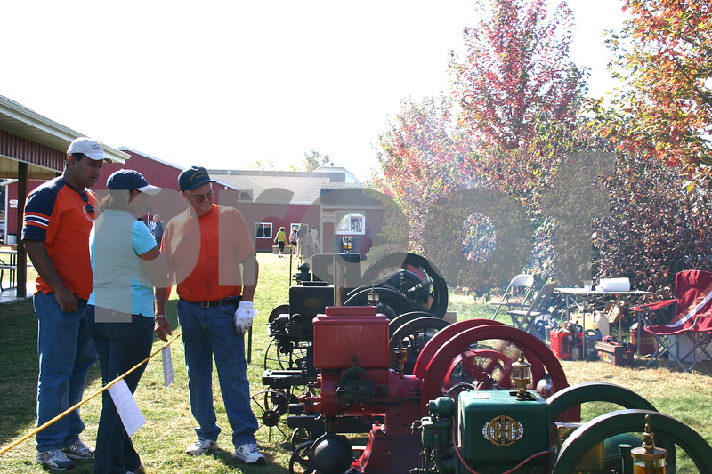 Antique gas engine collector Glen Helling of Plano explains the machines to Raj and Meena Patel of Bloomingdale Sunday at Jonamac Orchard in Malta. The antique farm show featured several types of gas engines that were used on farms in the late 1800s and early 1900s.<br /> <br /> Caitlin Mullen - cmullen@daily-chronicle.com