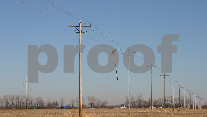 Dana Herra dherra@daily-chronicle.com<br /> <br /> A helicopter carries a new utility pole to its location in a field on East Sandwich Road Monday. ComEd used the helicopter to replace 62 poles snapped during wind storms in October.
