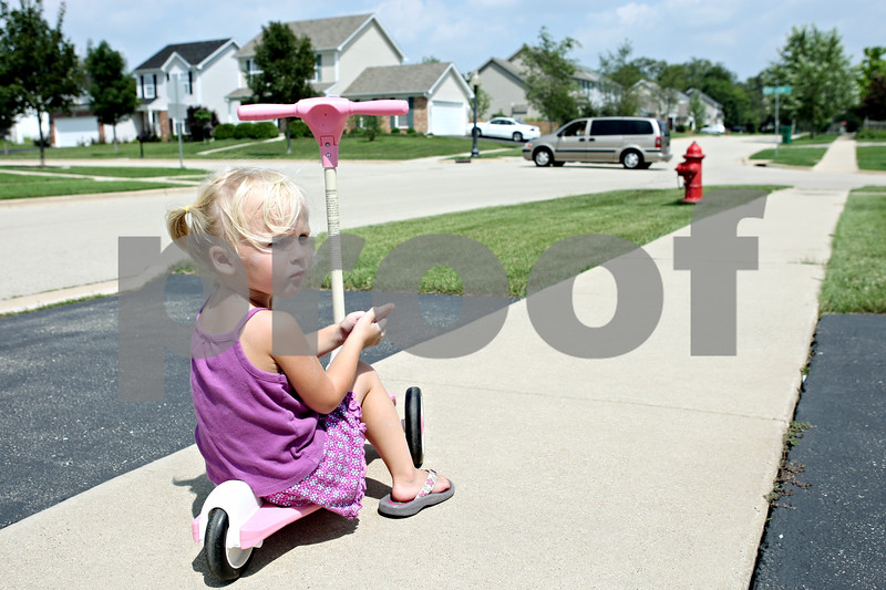 Rob Winner – rwinner@daily-chronicle.com<br /> <br /> 2-year-old Lily Minalga plays on the sidewalk in front of her home as a vehicle passes through the intersection of Kensington Boulevard and Bush Street in Dekalb, Ill. on Friday August 6, 2010. Recently, a group of residents living in Kensington Pointe subdivision in DeKalb petitioned to have a traffic study done to make a four-way stop at the intersection.