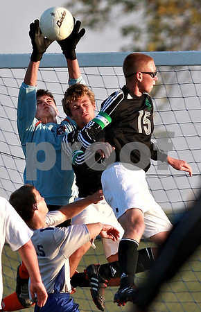 Beck Diefenbach – bdiefenbach@daily-chronicle.com<br /> <br /> Hinckley-Big Rock goal keeper Justin Salazar (left) stops the ball above Earlville-Leland's Reed Goodbred (15, right) and Chris Collins (3) during the second half of the Little 10 Conference tournament game at H-BR High School in Hinckley, Ill., on Wednesday Oct. 6, 2010. H-BR defeated Earlville-Leland 2 to 1 in double overtime.