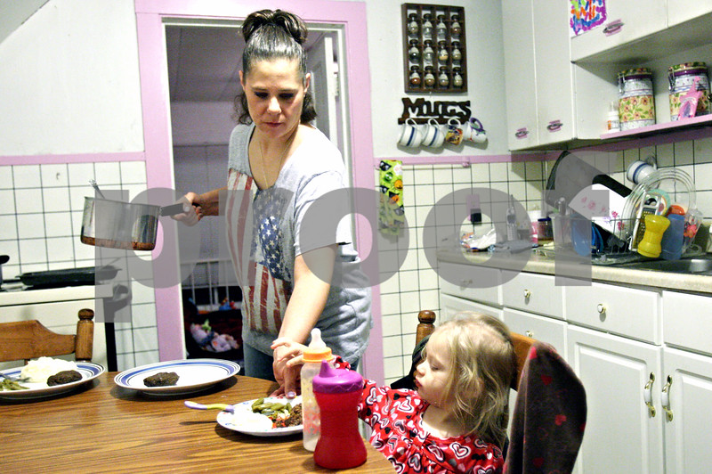 Rob Winner – rwinner@daily-chronicle.com<br /> <br /> Elizabeth Kopec serves her daughter Alexes (CQ), 2, a plate of hamburger, green beans and mashed potatoes at their Malta home on Wednesday. Kopec, a mother of two, has a LINK card which was not credited at the beginning of the month.