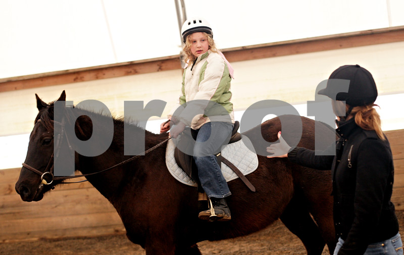 Beck Diefenbach - bdiefenbach@daily-chronicle.com<br /> <br /> Abbey Malaszewski (center), of Cortland, rides Beau as her coach Abbie Jossart gives gives her a riding lesson at Runaway Ranch in Sycamore, Ill., on Tuesday March 9, 2010. Teaching riding lessons helps Jossart pay the costs for owning her own horse.