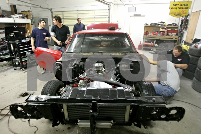 Rob Winner – rwinner@daily-chronicle.com<br /> <br /> At RPM Restorations in DeKalb on Wednesday evening, friends of the Koker family work on restoring a 1970 Buick Skylark for Jessica Koker, who currently serves in the United States Navy.