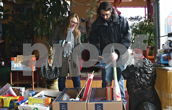 Dana Herra dherra@daily-chronicle.com<br /> <br /> Sarah Doll and Alex Huyser add toys to boxes filled with donations at a benefit concert held at The House cafe on Sunday. Admission to the concert, celebrating its 41st year, was a donation to Toys for Tots.