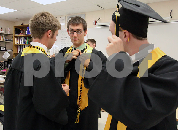 Wendy Kemp/For The Daily Chronicle<br /> Ryan Frederick, Greg Forsyth and Chris Handel (l to r) adjust their hats and gowns before the graduation ceremony at Sycamore High School on Sunday.<br /> Sycamore 5/30/10
