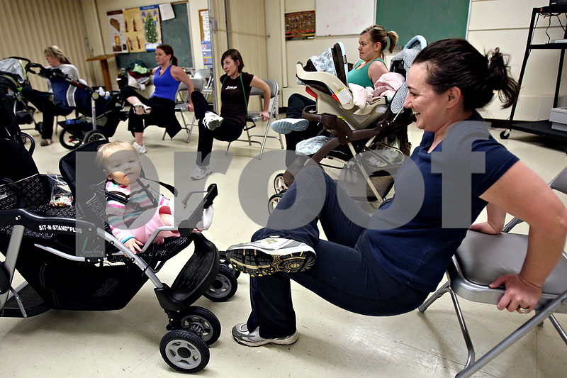Rob Winner – rwinner@daily-chronicle.com<br /> 9-month-old Sydney sits quietly in her stroller as her mother, Kristen Young, of Genoa, participates in a work out program called Stroller Strides in the basement of Immanuel Lutheran Church in DeKalb, Ill. on Saturday January 9, 2010.
