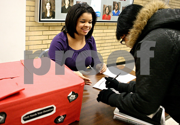 Rob Winner – rwinner@daily-chronicle.com<br /> Haitian-American NIU student Sarah Theodore-Young (left) accepts a donation from Ashley Mayfield on Thursday January 28, 2010 at the Holmes Student Center in DeKalb, Ill. Sarah Theodore-Young is leading a local relief effort for those in need after a devastating earthquake in Haiti.<br /> <br /> DeKalb, Ill. <br /> Thursday January 28, 2010