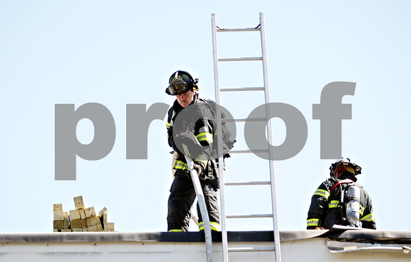 Beck Diefenbach  -  bdiefenbach@daily-chronicle.com<br /> <br /> DeKalb fire fighters work on the roof of the 3100 building of Lincolnshire West Apartment complex in DeKalb, Ill., on Thursday July 1, 2010.